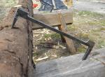 Tesařská kramle - hroty kramle jsou vůči sobe pootočeny o 90° tak, aby se daly snáze zabít do podélných vláken tesané klády a tesařské kozy pod ní.